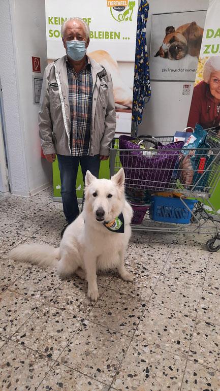 Mann mit weißem Schäferhund und Tierfutterspenden