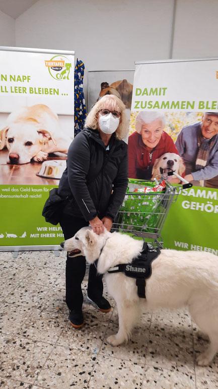 Frau mit weißem Schäferhund und Tierfutterspenden