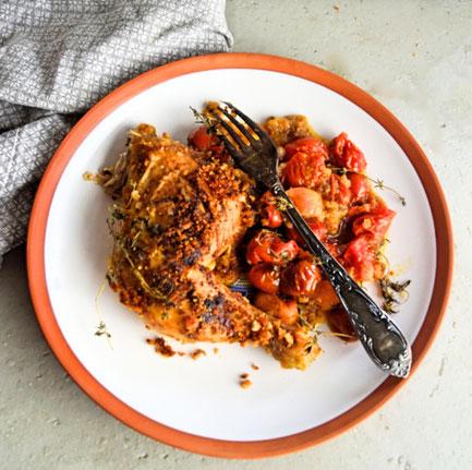 Knuspriges Hähnchen aus dem Backofen mit Bröselkruste und bunten Tomaten