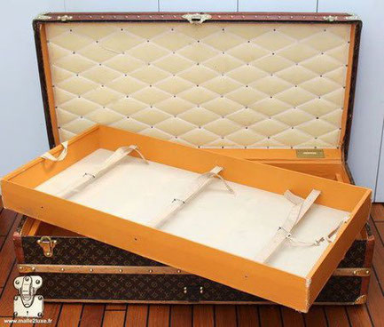 Interior of the Louis Vuitton cabin trunk, stencil canvas.  With a removable locker with 3 straps. interior in orange vuittonite. Padded cover , white ribbon signed Louis Vuitton. 1925