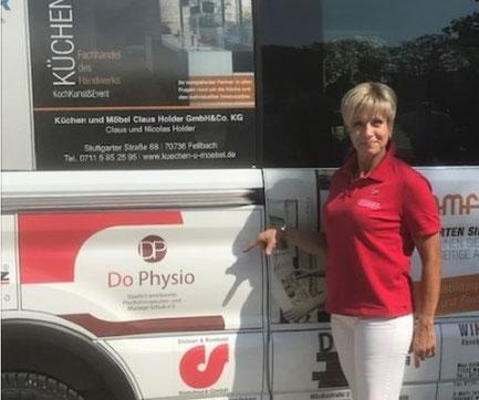 Frau steht vor einem Bus mit einer DoPhysio Werbung