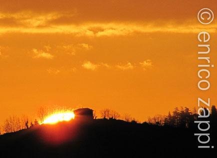 L'alba del 27 gennaio 2012, il sole fa capolino a fianco di una casetta in cima alla collina. Sembra quasi che gli alberi adiacenti s'infiammino tanto è il bagliore dell'astro nascente!