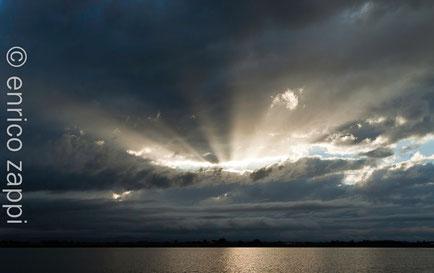Raggi di luce solare filtrano dalla grigia e fitta coltre di nubi sulle Saline di Cervia.