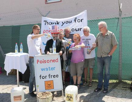 """Unsere heutige Aktion vor der US-Kaserne in Katterbach, auf dem zu sehen ist, wie OLA-Mitglieder """"Uncle Sam"""" symbolisch das verseuchte Trinkwasser aus Ansbacher Hausbrunnen vor die Füße kippen."""