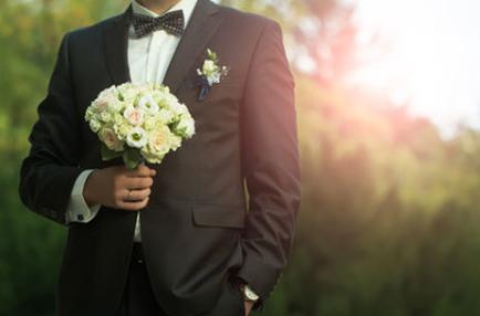 Bräutigam in Anzug und Fliege mit Brautstrauß und Herrenanstecker am Revers