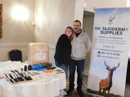 Image shows Jessica, NK Taxidermy Supplies owner, and her father, David, North Kerry Taxidermy owner. On their right, a table of Jessica's stock, and on their left, a banner advertising NK Taxidermy Supplies.