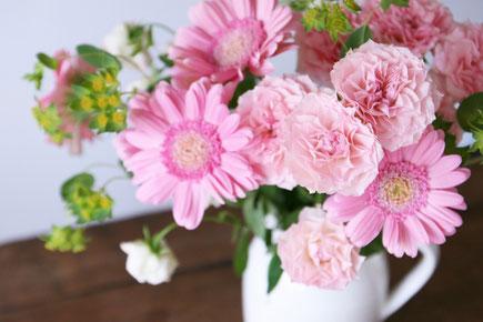 白の花びんに活けられたピンクの花たち。デイジーとカーネーション。