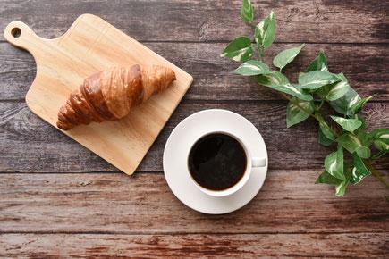 広げられたノートと白のボールペン。カモミールの花とハーブティーの入ったカップ&ソーサ。