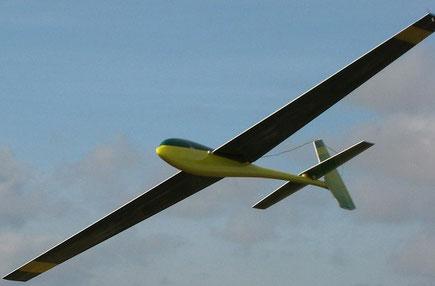 planeur radiocommandé Coquillaj Aeromod jaune et vert, en vol, sur fond de ciel nuageux