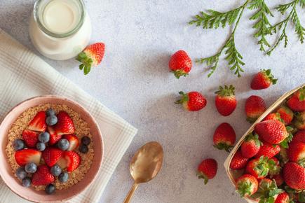ピンクのノートパソコン。広げられたリングノートとボールペン。ピンクの腕時計。ピオニーの花。