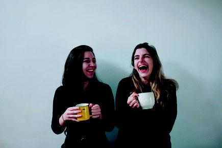 Das Bild zeigt die Herausgeberinnen Rebecca Buxton und Lisa Whiting, lachend mit einer Kaffeetasse in der Hand.