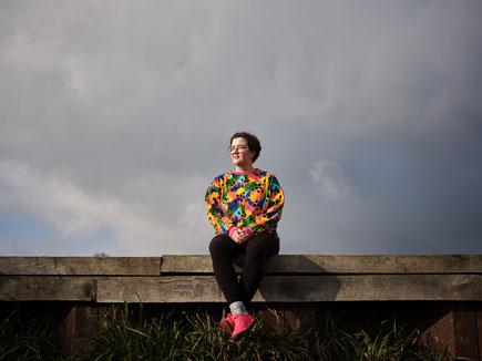Das Bild zeigt die Autorin Katharina Volckmer auf einem Holzsteg sitzend.