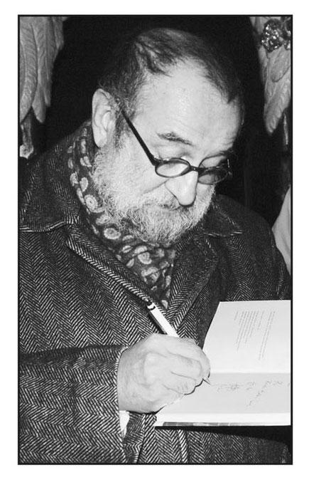 Das Buld zeigt den Autor Said, wie er ein Buch signiert.