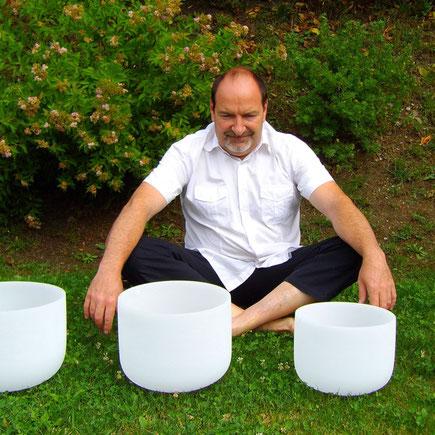 Alain Métraux assis avec des bols de cristal