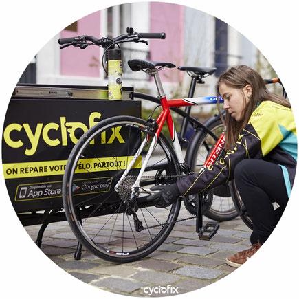 réparation de vélo dans la rue à Paris