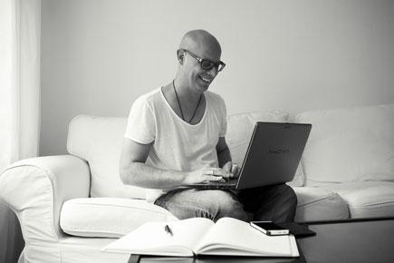 Bild von Mirko Kussin mit Laptop auf dem Schoß, arbeitend.