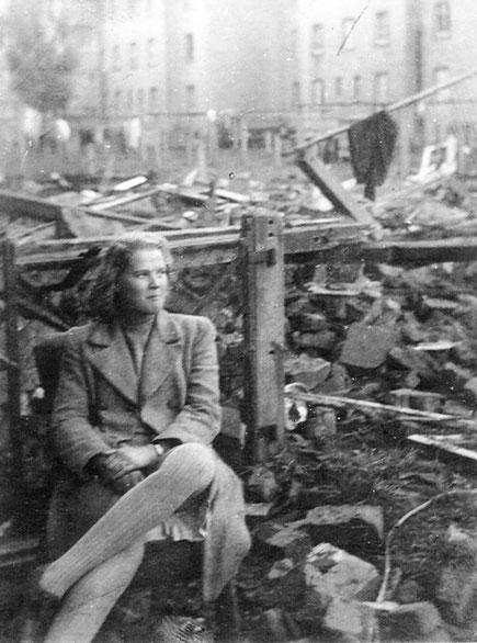 Mit Fassungslosigkeit schaut die junge Frau auf die Trümmer
