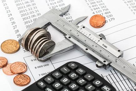 Das Budget muss genau kalkuliert werden. Das Geld ist in einem Messgerät eingespannt und wird mit dem Taschenrechner nachgerechnet