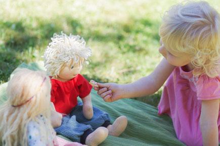 Waldorfpuppen sitzen beim Picknick. Ein Mädchen füttert die handgemachten Stoffpuppen nach Art der Waldorfpuppe