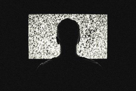 Mann sitzt vor Fernseher mit Störung