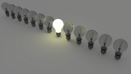 Eine leuchtende Glühbirne unter vielen