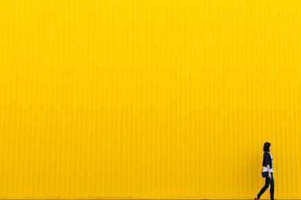 Frau vor gelber Wand gehend