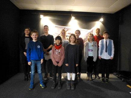 Auf einer schwarz gehaltenen Bühne stehen acht Kinder sowie die Klavierlehrerin Katja Poljakova und der Geigenlehrer Valentin Dübbers von der MusikInsel.