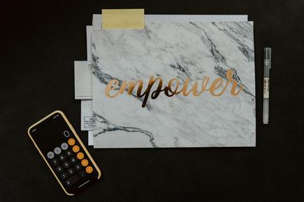 """Notizbuch mit der Aufschrift """"Employer"""", ein Taschenrechner und ein Stift"""