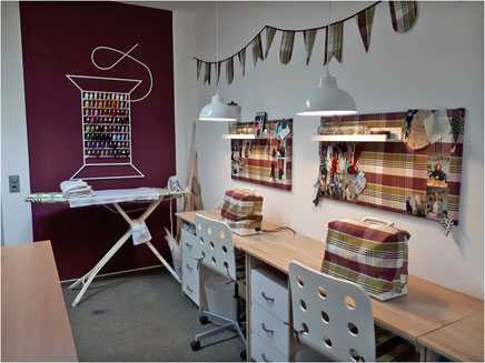 Nähschule ganz vernaht, Arbeitsplätze mit Nähmaschinen und lila Wand