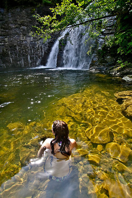 Young woman swimmer kneels in the water by Trent River falls in the Comox Valley.