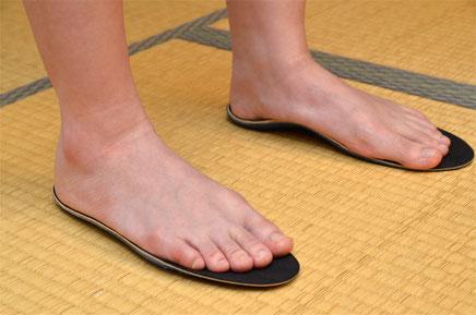 足の下にある黒い敷物が「アーチサポートインソール」です