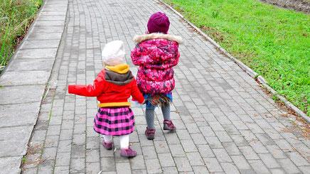 Kleine Zwillingsmädchen, warm verpackt, im Garten