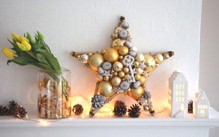 Stern aus goldenen Glaskugeln und weißem Holzschlüssel mit Tulpen und Windlichtern zusammen dekoriert.
