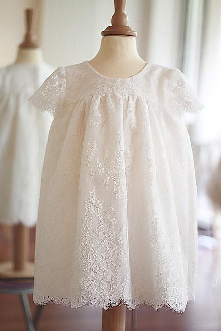 Robe de baptême bébé fille courte en dentelle italienne doublée soie. Fait-main dans l'atelier Fil de Légende à Neuilly-sur-Seine. Envois dans toute la France.