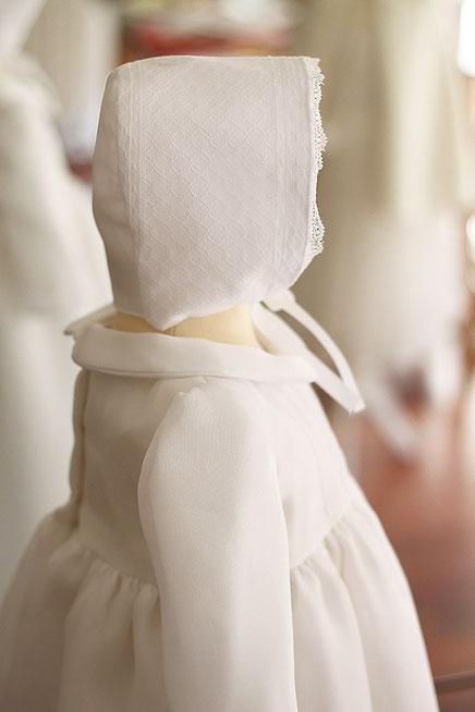Bonnet de baptême en dentelle de Calais doublée coton. fait-main dans l'atelier Fil de Légende à Neuilly-sur-Seine.