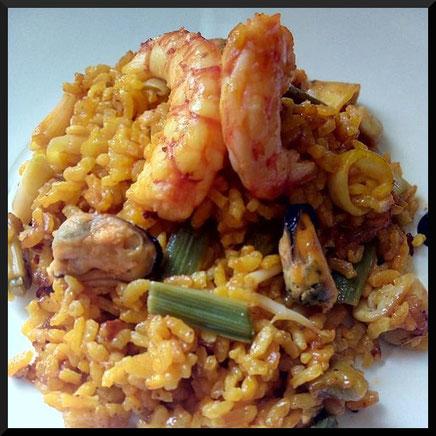 Paella arroz y marisco con ajos tiernos típica de la gastronomía valenciana.
