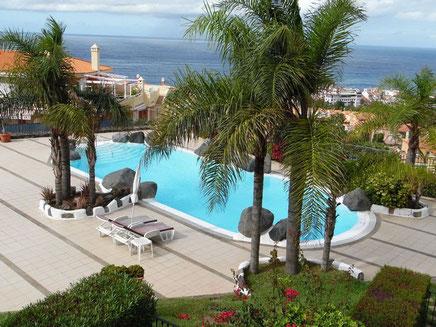 Auf dem Bild sieht man den abgerundeten Pool der  Wohnanlage und im Hintergrund das Meer.