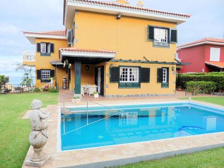 Einfamilien-Immobilie mit Pool und Haus dahinter.