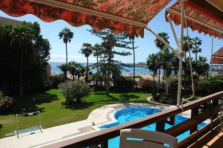 Blick vom Balkon in den Reich bepflanzte Gemeinschaftsgarten mit Pool und dem Strand im Hintergrund.