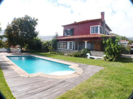 Große Rasenfläche mit Blumenrabatten fassen die Villa ein mit einem unglaublichen Blick auf das Meer.