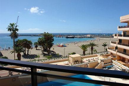 Gemütlicher Balkon mit Sitzmöbeln und Blick in die Umgebung bis zum Meer.