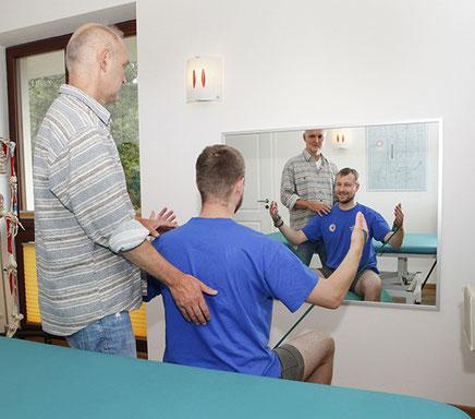 Physiotherapeutische Behandlung in schönem, lichtem Raum mit blauer Liege