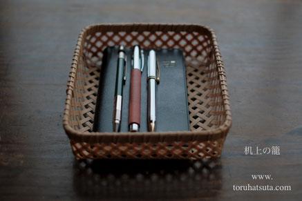 机上の籠に手帳と筆記具を収めて