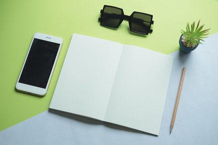テーブルに広げられたスクラップブック。無造作に置かれた花たち。押し花。