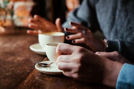 Abgebildet sind zwei Tassen Kaffee auf einem rustikalem Tisch. Dazu Hände einer Frau und eines Mannes. Beide tragen blaue Kleidung. Die Hände der Frau sind offen und sie scheint etwas zu erläutern. Die linke Hand des Mannes hebt seine Tasse Kaffee an.
