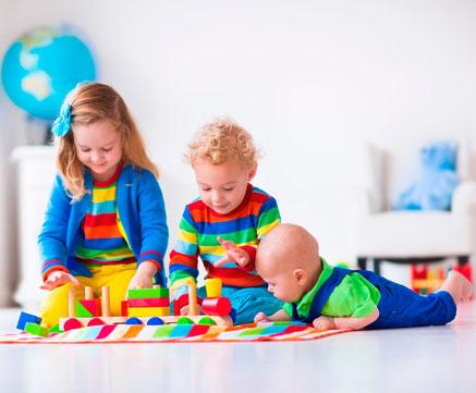 Kinder verschiedenen Alters spielen auf dem Fußboden