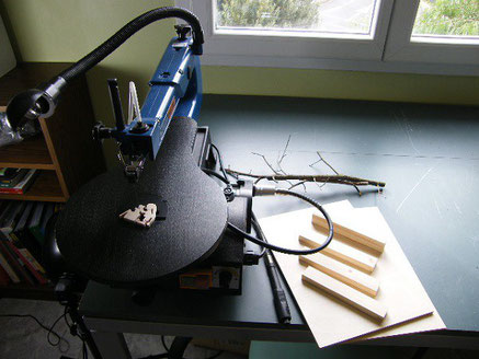 photo d'une scie à chantourner dans un atelier, avec un personnage découpé en présentation dessus