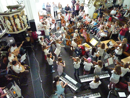 Von einer Empore aus sieht man in einen Altarraum, in dem zahlreiche Kinder mit Instrumenten sitzen und stehen. Sie spielen auf elektronischen Klavieren, Gitarren, Geigen, Akkordeons vor einem  großen Publikum.