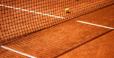 Tennisplatz mit Tennisball und Tennisnetz das Schatten wirft