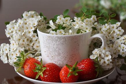 パソコンのキーボードの前に広げられたビジネスグッズ。花柄の手帳と電卓、スマホ、イヤホン、ボールペン、マスキングテープ。